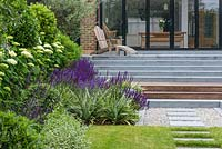 View past flowerbed up steps to terrace outside modern extension.