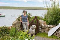 Sue Palmer in her seaside front garden overlooking Widewall Bay on South Ronaldsay, with Ollie the collie dog.