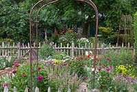 Metal arch sitting among cut flower beds.