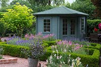 A summerhouse overlooking a Buxus parterre filled with clary sage.