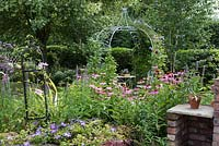 View across flower border including Echinacea - coneflowers - and Agastache to an ornate