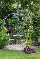 Ornate metal gazebo or arbour above a circular patio with table and chairs. Climbers such as 