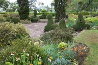 View across sunken paved garden with unusual topiary shapes