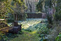 Old garden rollers, with naturalised snowdrops and winter aconites