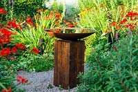 Bird bath of oak sleeper pedestal and mild steel bowl surrounded by Crocosmia 'Lucifer at  Veddw House Garden, Monmouthshire, Wales, UK.