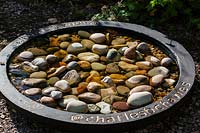 Birdbath with pebbles on ground at  Veddw House Garden, Monmouthshire, Wales, UK.