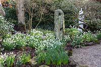 Stone sculpture underplanted with Galanthus. York Gate garden, Leeds, UK.