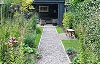 View down long pebble path to cosy garden seating area at the back of shed.