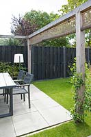 Garden patio and dining area surrounded by wooden pergola with wicker screens.