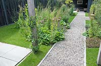 View down gravel pathway in narrow, modern garden.