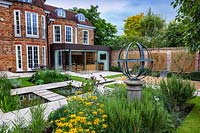 View accross Armillary Sundial and pond to the rear of the house. Garden design by Peter Reader Landscapes.