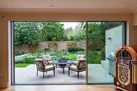 View from the inside out to terrace with table and chairs. Garden design by Peter Reader Landscapes.