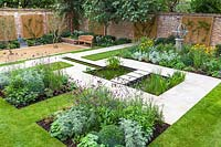 View of pond and stepping stones, surrounded by mixed beds and Armillary Sundial in walled city garden. Garden design by Peter Reader Landscapes.