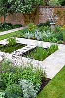 View of formal pond with rill, surrounded by mixed beds with Armillary Sundial in walled city garden. Garden design by Peter Reader Landscapes.