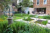 View of Armillary Sundial in modern city garden with pond. Garden design by Peter Reader Landscapes.