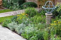 Armillary Sundial in mixed bed. Garden Design by Peter Reader Landscapes.