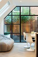 View through living room to courtyard with Bamboo and shrubs, London
