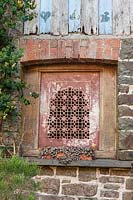 Decorative carved stone window from India. Plaz Metaxu Garden, Devon, UK.
