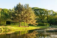 Lake surrounded by trees and lawn, Plaz Metaxu Garden, Devon, UK.