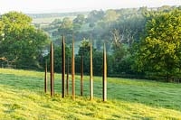 Metal sculpture in the form of standing stones, Plaz Metaxu Garden, Devon, UK.