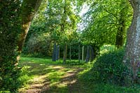 Circle of standing stones among trees. Plaz Metaxu Garden, Devon, UK.