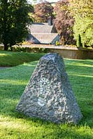 Stone with footprint at the entrance. Plaz Metaxu Garden, Devon, UK.