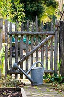 Watering can at garden gate.