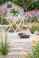 Ornate metal table and chairs on circular patio in gravel garden