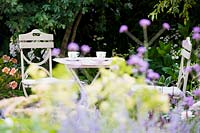 Seating area in cottage garden surrounded by soft, pastel summer flowers. Best of Both Worlds garden, Sponsored by BALI, RHS Hampton Court Palace Flower Show, 2018.