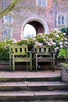 Wooden seats with pink rhododendron and historic gatehouse at Hodsock Priory, Blyth, Nottinghamshire