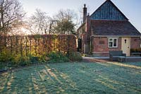 Morning sun on frosted lawn with beech hedge and house, Stockbridge, Hampshire