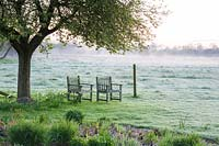 Mist rising at dawn with chairs below tree beside fence, Stockbridge, Hampshire