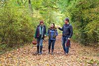 Women and man on autumnal walk on woodland path.