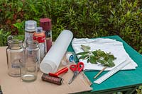 Tools and materials for making leaf-printed candle holder decorations.