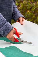 Woman cutting length of tracing paper with scissors.