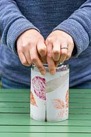 Woman wrapping leaf-print decorated paper around glass jar.