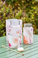 Collection of glass jars decorated with leaf prints to use as candle holders.