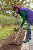 Woman raking empty border by patio to create a fine tilth.