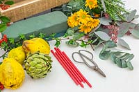 Tools and materials for creating autumnal floral candle arrangement.