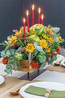 View of completed autumnal floral candle arrangement on set table, with seeded Eucalyptus, Rosemary, Globe Artichokes, Cotoneaster and Chrysanthemum.