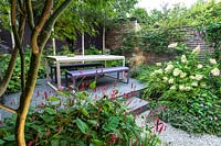 View from under the Acer palmatum to table and bench in small urban garden. Designed by John Davies Landscape.