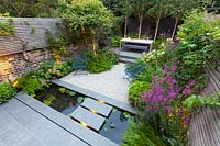 View of illuminated stepping stones over narrow garden pond at dusk. Garden design by John Davies Landscape.