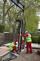 Pavilion parts are lowered into place in preparation for RHS Chelsea Flower Show