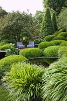Pool and seating with Buxus, Carpinus betula - Hornbeam and Hakonechloa. Irish Sky Garden, RHS Chelsea Flower Show.