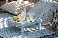 Small outdoor side table, surrounded by cushions for seating.