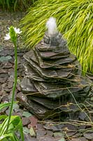 Piled slate water feature in gravel garden.