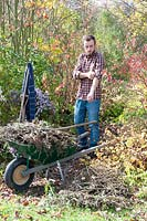 Man clearing garden cuttings in the autumn.