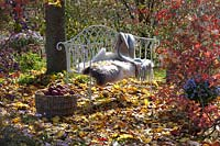 Garden bench with fur blanket under a tree, surrounded by autumnal leaves.