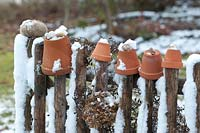 Clay pots with snail shells and snow on garden fence.