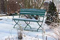 Bench in the snowy garden